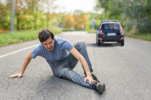 man sitting on road holding ankle